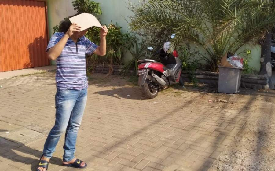 Salah seorang warga menutupi kepalanya akibat suhu panas di siang hari.