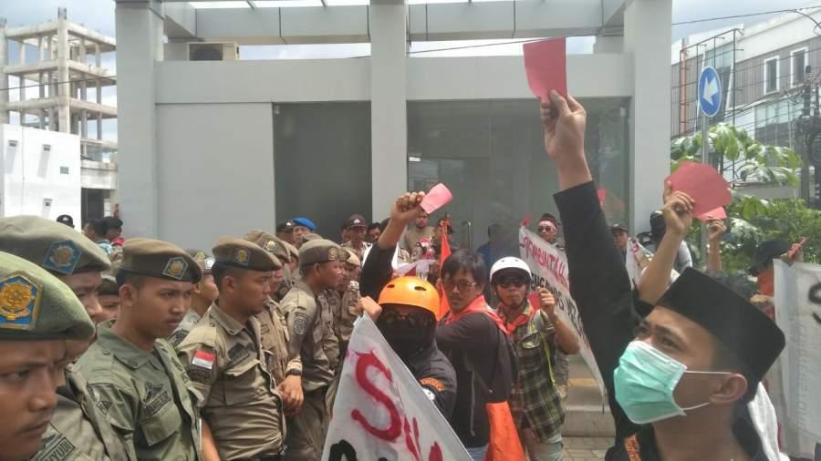 Aktivis lingkungan hidup saat menggelar aksi di Balaikota Tangsel. Nampak para aktivis menunjukan kartu merah yang diarahkan ke pemerintah setempat.